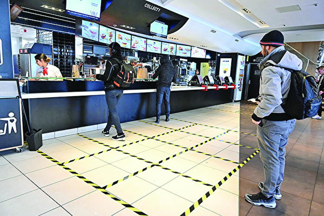 英國一家麥當勞店裏「保持社交距離」的顧客。(JUSTIN TALLIS/AFP/via Getty Images)