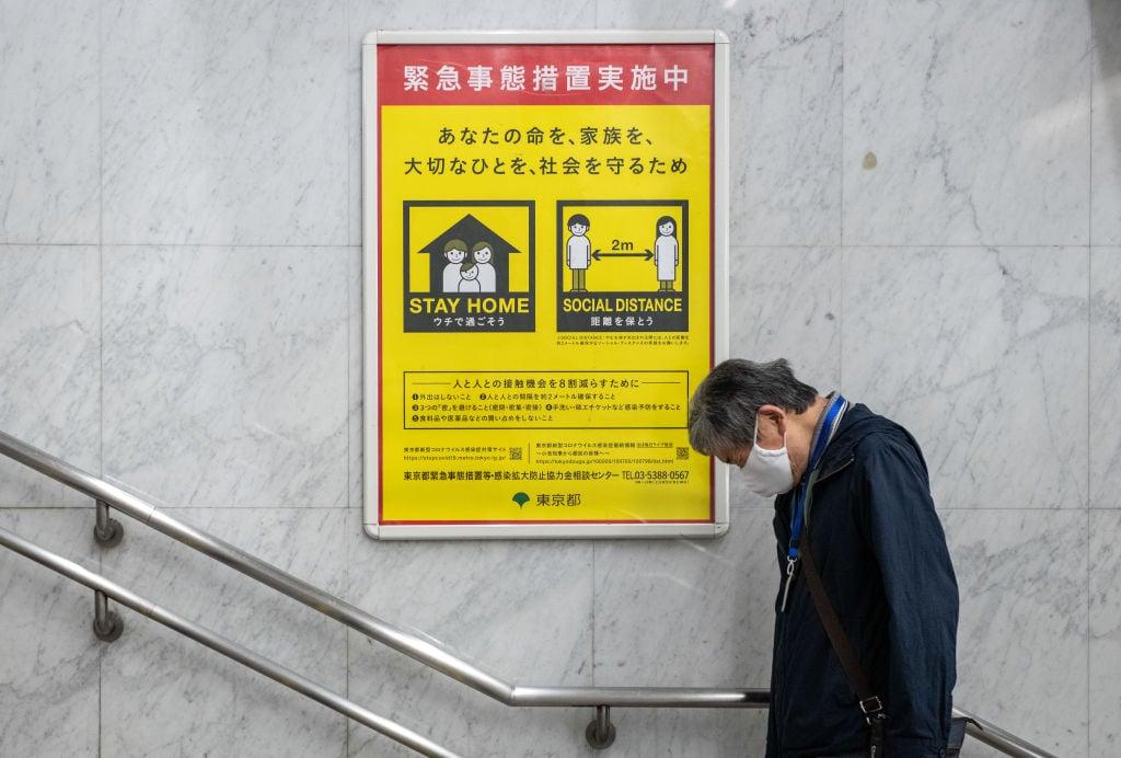 2020年4月28日,日本東京,一個戴著口罩的人走過一條告示,告訴人們留在家裏或保持社交距離。(Carl Court/Getty Images)