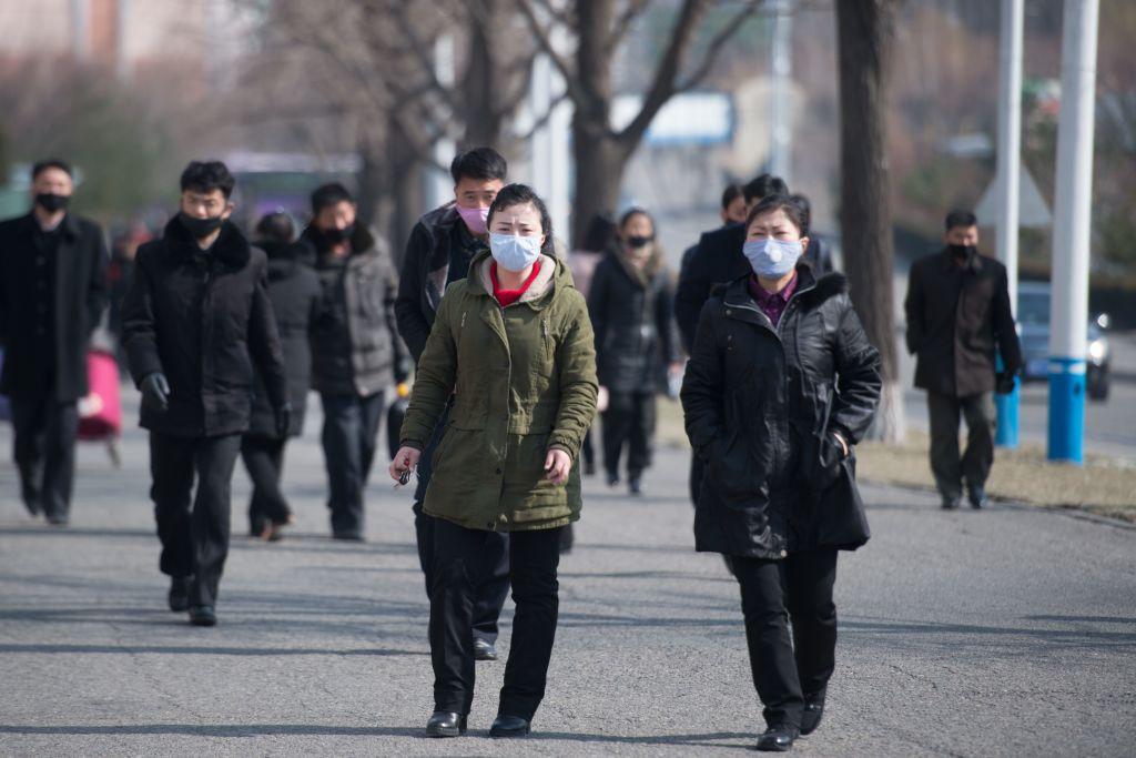 圖為,2020年2月26日,民眾戴著口罩走在平壤的街道。(KIM WON JIN/AFP via Getty Images)