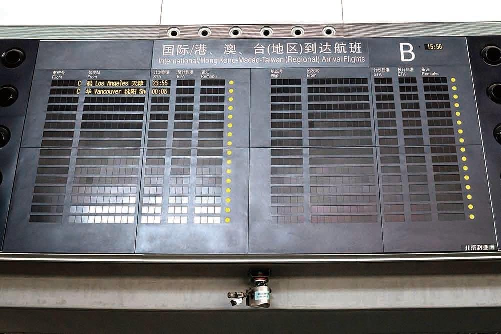 4月13日,北京首都國際機場的看板一片黑,只有兩個航班,分別是從洛杉磯到天津、從溫哥華到瀋陽。(AFP)