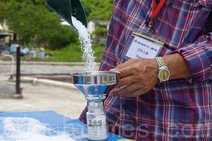 David嫻熟地拿起漏斗,將粒粒海鹽灌注入透明玻璃樽中。(曾蓮/大紀元)