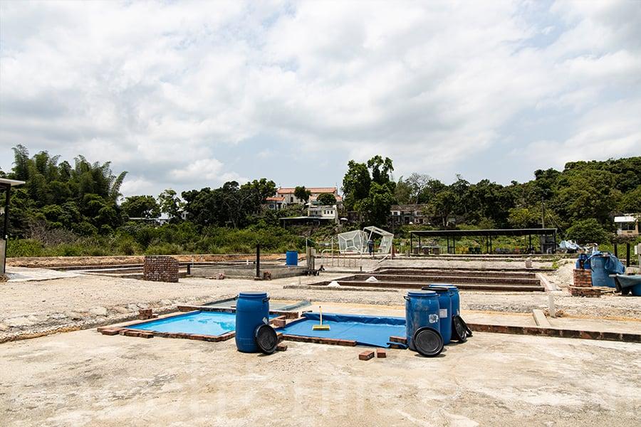 下雨時為了保存高鹽份的「滷水」,團隊成員使用大水桶盛裝。(陳仲明/大紀元)