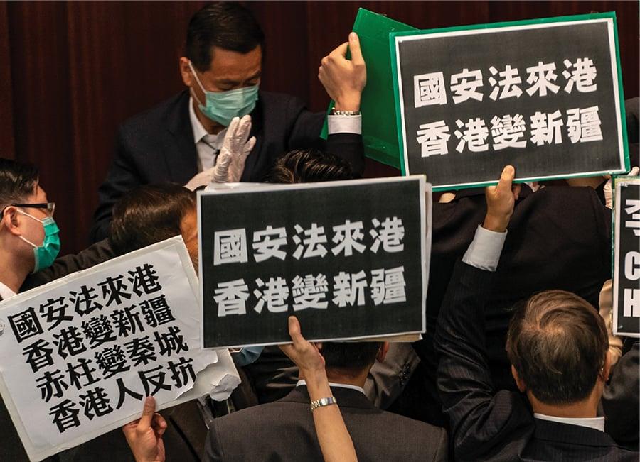 當林鄭月娥轉稱為「市長」的一剎那,就是全球制裁中港之時。香港本擁有世界認可的穩定貨幣、法治系統及宗教信仰自由等,適合定鼎為亞太區總部。美商會批「港版國安法」含糊,損港金融中心基石,增外商風險,中共此舉無疑自毀長城。圖為日前泛民議員於立法會內抗議反對「港版國安法」。(PHILIP FONG/AFP via Getty Images)
