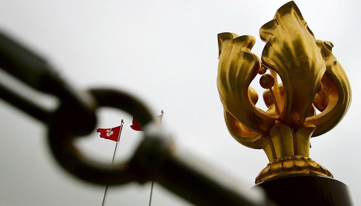 圖為香港維多利亞港沿海的金紫荊廣場上象徵香港的大型雕塑「金紫荊」,以及通過鎖鏈空洞看到的香港特別行政區區旗。 (Guang Niu/Getty Images)
