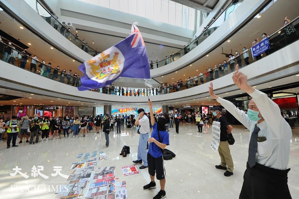 5月29日中午1時許,過百市民中環IFC「和你lunch」,有市民揮舞旗幟及展示標語。(宋碧龍/大紀元)