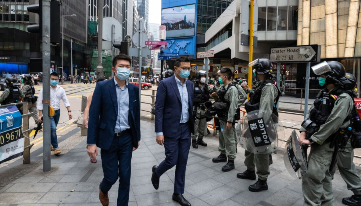 圖為香港大街上,2020年5月28日帶著口罩的香港市民從正在街道上戒備的防暴警察面前走過。(Billy H.C. Kwok/Getty Images)