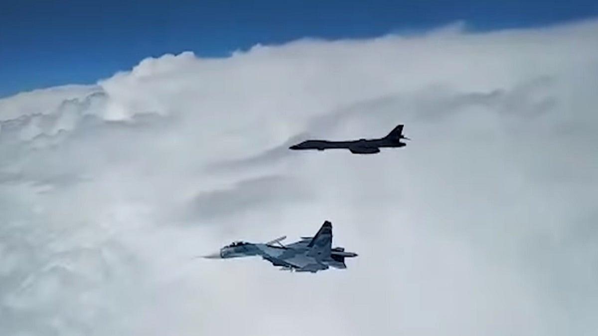 圖為,俄軍戰機(下)升空「伴飛」美軍B1B轟炸機(上)。(影片截圖)