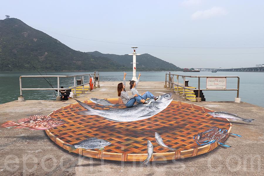 位於碼頭的巨型立體地畫生動繪出了日常所見的鹹魚。(受訪者提供)