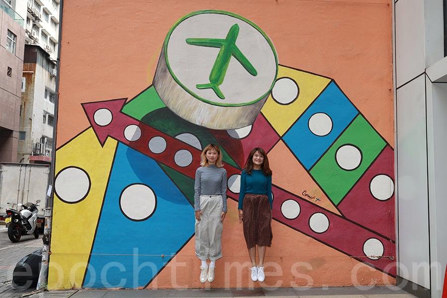 阿甘和Sandy在壁畫前拍攝「飛」主題的相片。(陳仲明/大紀元)