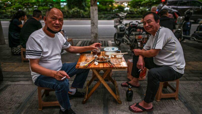 疫情導致中國經濟陷入困境,官方重啟地攤經濟。圖為武漢人吃地攤小吃。(HECTOR RETAMAL/AFP via Getty Images)