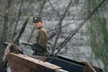 韓聯社報道,7月28日淩晨,在吉林省長白朝鮮族自治縣,5名持槍搶劫的北韓軍人與前來抓捕的大陸軍警爆發槍戰。目前有兩名疑犯被捕,3人在逃。圖為中朝邊境的北韓士兵。(Frederic J. BROWN/AFP)