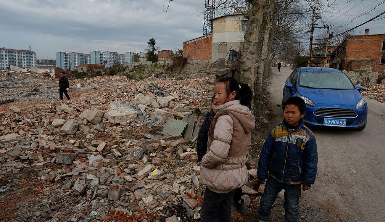 2014年2月20日拍攝於中國貴州省安順市郊區的這張照片上,近處是幾個農民的孩子,遠處是為安置強制搬遷的村民修建的公寓建築。(MARK RALSTON/AFP via Getty Images)
