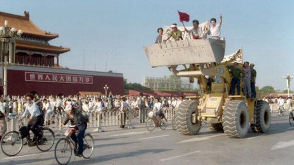 圖為當年六四事件時,一輛推土機上坐著幾位民眾在廣場上遊行。(CATHERINE HENRIETTE/AFP/Getty Images )