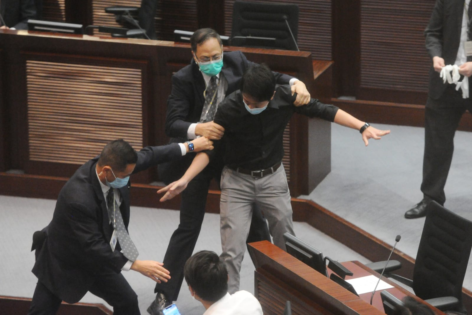 民主黨許智峯亦步出座位進行抗議,但被在場保安攔阻。期間,許智峯手中膠樽 跌落在地,會議室內充斥一陣臭味。(宋碧龍/大紀元)