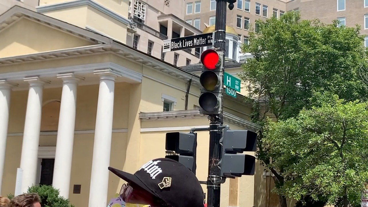 新街名Black Lives Matter Plaza。街名後的淡黃色教堂就是特朗普本周早前造訪的St. John's教堂。新街標的顏色用的是黑色,與DC通常的綠色街名標誌不同。(吳芮芮/大紀元)
