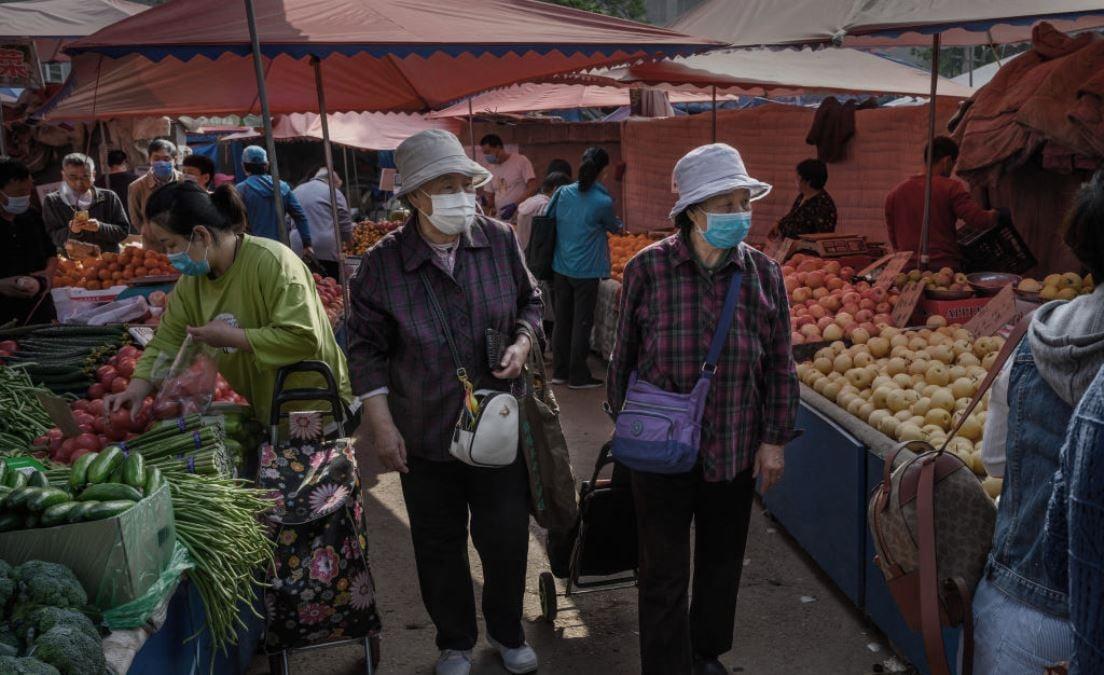 圖為2020年4月30日中國北京市民眾戴著口罩在一處露天市場購物的場景。(Kevin Frayer/Getty Images)