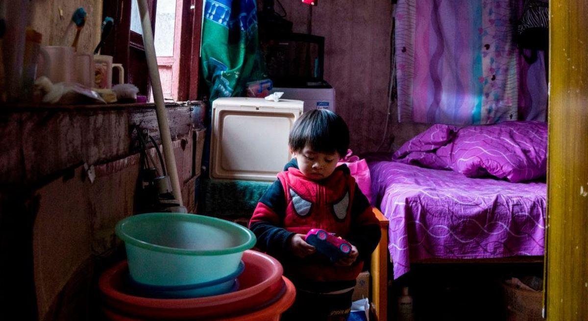 圖為2017年12月26日,中國上海市老西門貧困農民工的一個孩子在擁擠雜亂的家中玩玩具。(CHANDAN KHANNA/AFP via Getty Images)