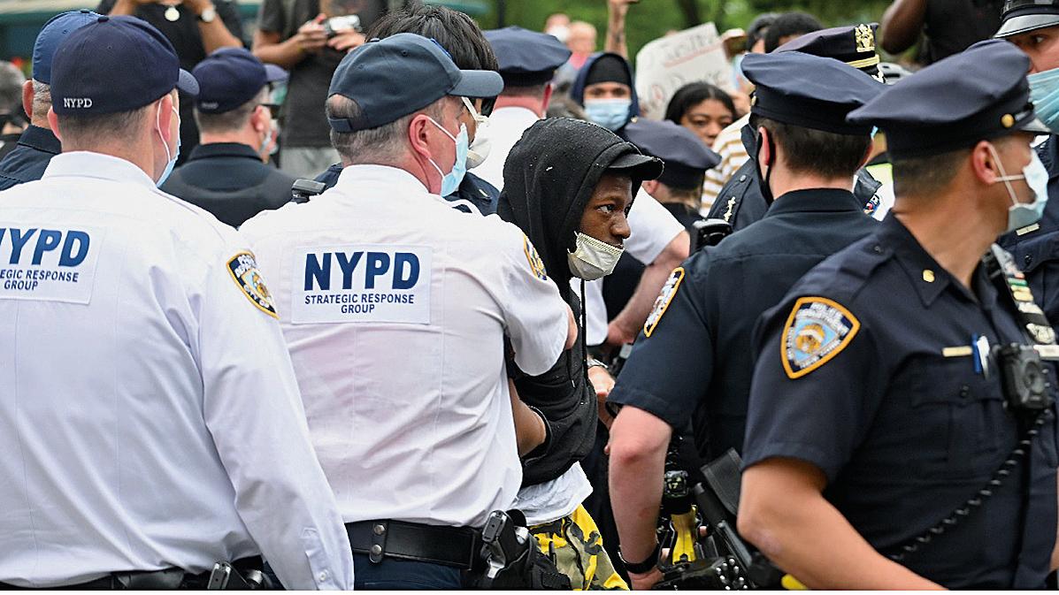 白宮發言人麥肯納尼於周一(6月8日)白宮記者會上轉達特朗普意見,表示不贊成對警察撤資或解散警局。圖為5月28日,紐約市警察在抗議現場維持秩序。(AFP)