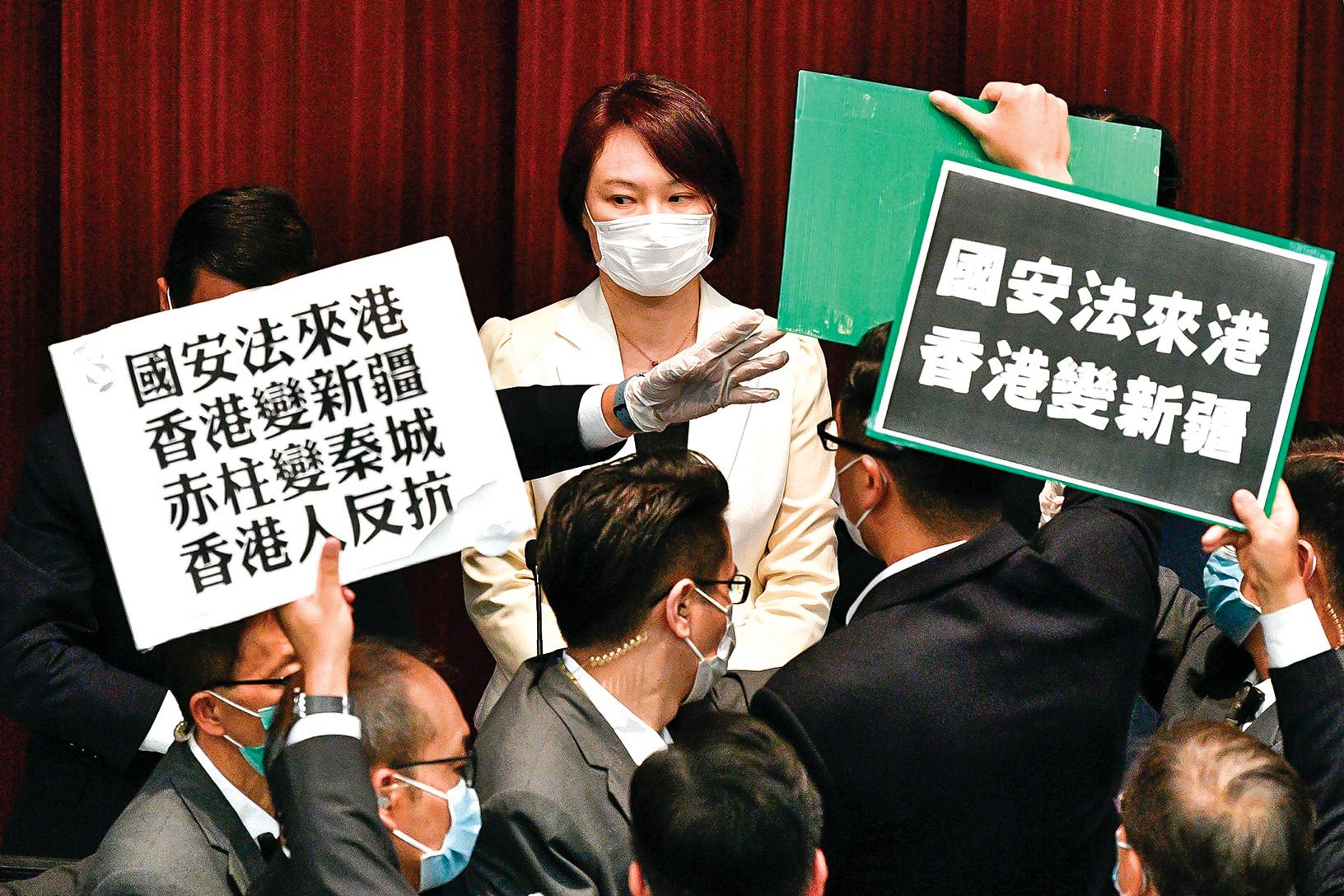 5月22日在香港立法會場,民主派議員舉牌抗議港版國安法的提案。(Getty Images)