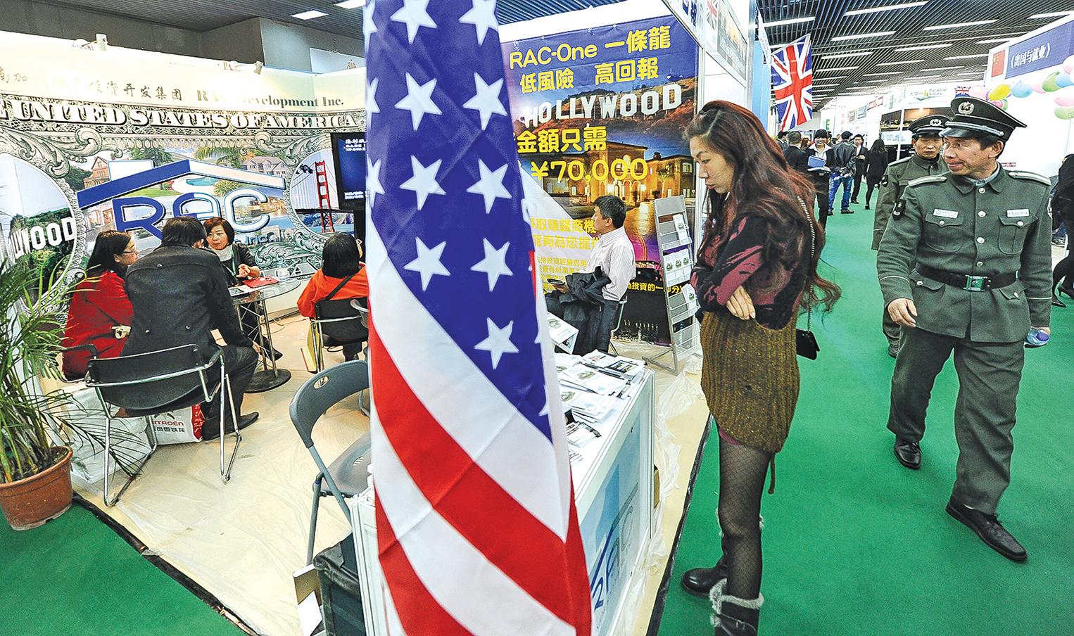 嘴裏說社會主義好的香港有錢人,在紐約、倫敦、溫哥華買房子、拿身份。因為他們需要的是自己的生命權、自由權、財產權的安全。圖為2012年4月在北京舉行的海外和中國房地產博覽會上,人們在關注美國房地產。(Getty Images)