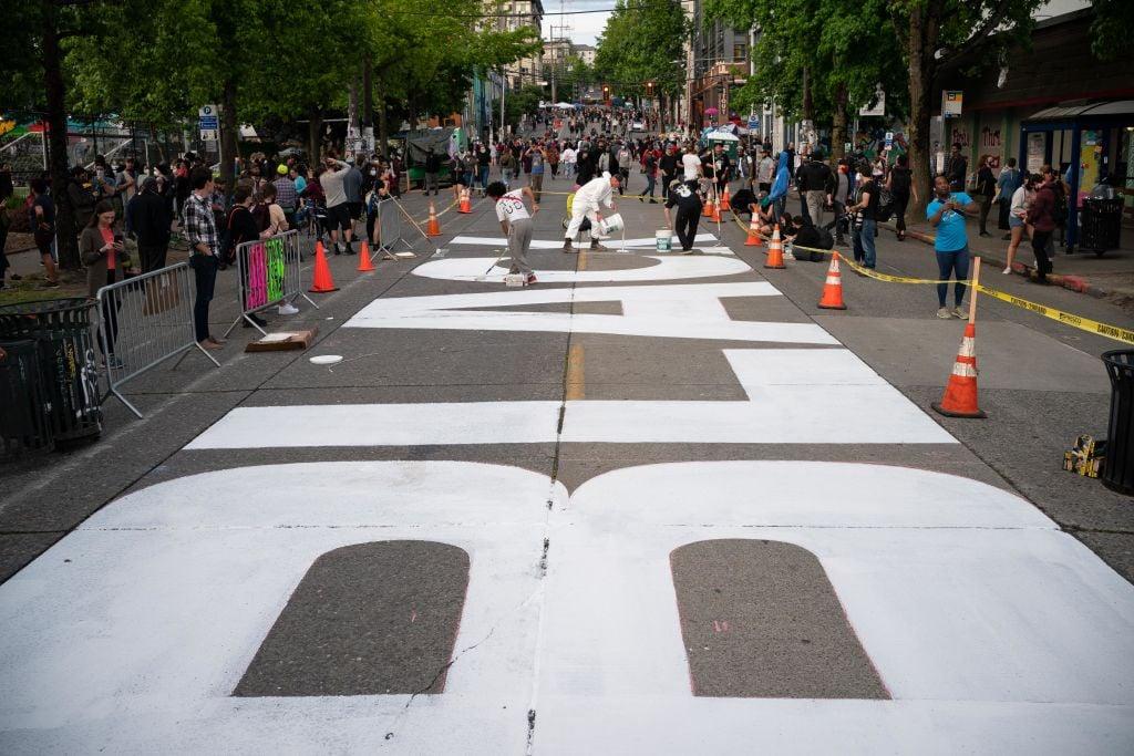 2020年6月10日,西雅圖「國會山自治區」(CHAZ)內的抗議者在地上塗寫「黑命貴」。(David Ryder/Getty Images)