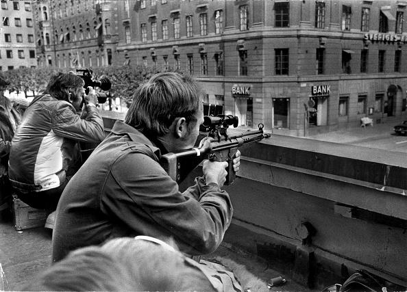 1973年8月24日,斯德哥爾摩一宗銀行劫案演變成長達6天的警匪對峙。人質在與經歷極度恐懼後,反認定警察是比劫匪更大的威脅而感恩劫匪,此種扭曲心理被命名為「斯德哥爾摩綜合症」。圖為一名攝影記者與一名警察射手,並肩守在Kreditbanken銀行對面的樓頂。(AFP PHOTO / SCANPIX SWEDEN / ROLAND JANSSON via Getty Image)