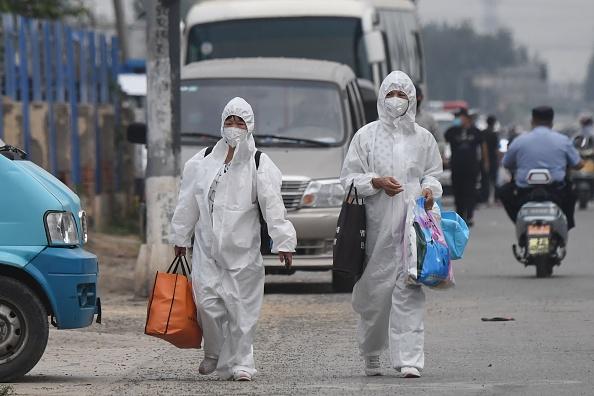北京新發地批發市場爆發群聚感染,市民已開始穿上防護服。(GREG BAKER/AFP via Getty Images)