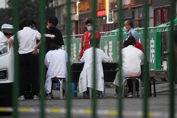 北京豐台區「新發地批發市場」爆發群聚感染,防疫人員進入市場排除檢測。(GREG BAKER/AFP via Getty Images)