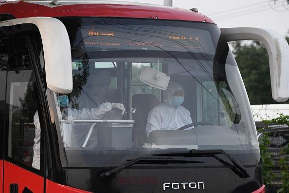 北京一輛大巴車上的司機等人都穿上了防護服。(GREG BAKER/AFP via Getty Images)
