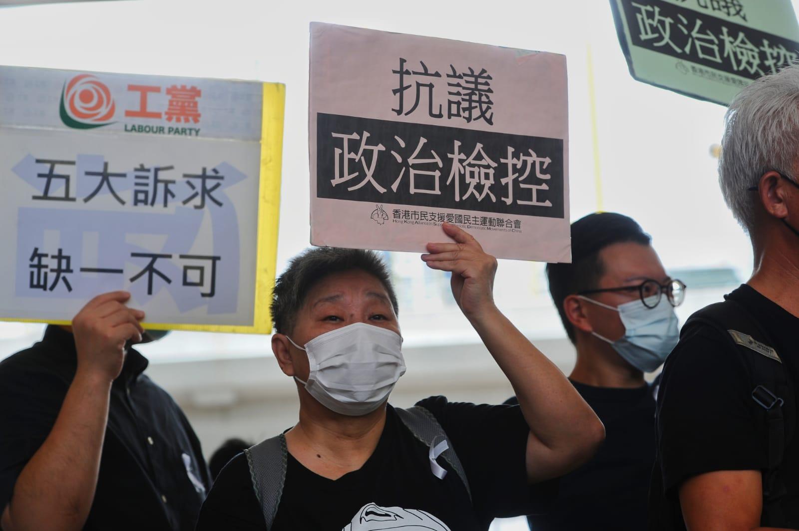 眾多民主派的支持者們也前來聲援,他們手舉「抗議政治檢控」、「保障公民權利,集會遊行自由」的標語,並高呼「廢除國安法」、「五大訴求,缺一不可」等口號。(宋碧龍 / 大紀元)