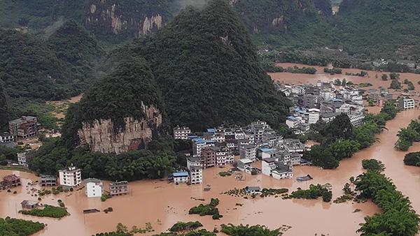 中國南方連日暴雨成災,多地被淹沒,許多人被沖走,大量房子倒塌。圖為6月7日廣西陽朔被洪水淹沒。(Getty Images)