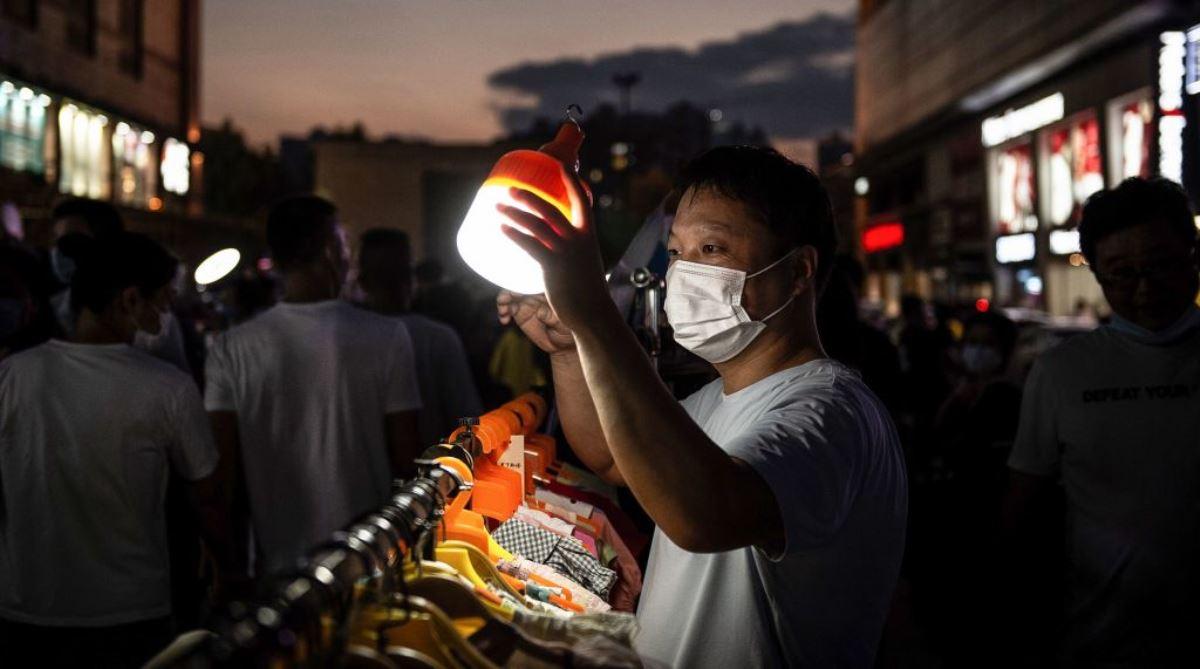 2020年6月10日中國湖北省武漢市一個戶外市場上,擺攤賣服裝的攤主正舉著燈等候顧客光顧。(STR/AFP via Getty Images)