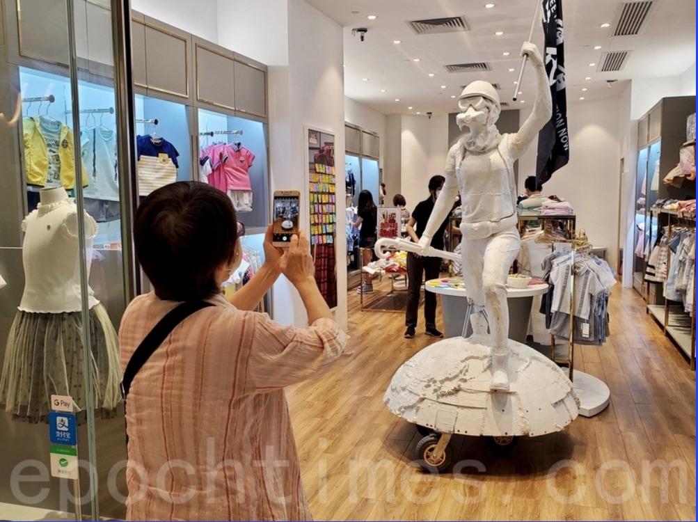一些客戶對著民主女神是拍照。(宋碧龍/大紀元)