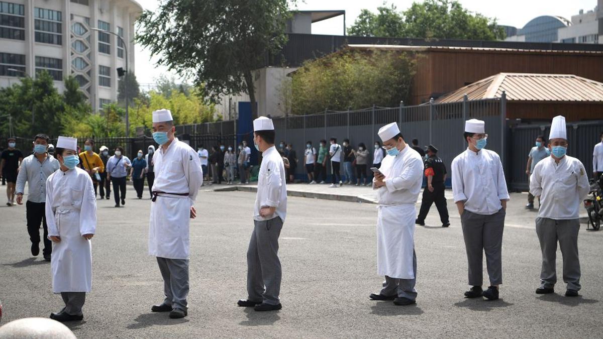 中共病毒疫情迅速蔓延,天津6月17日發現本土確診病例,患者在一家西餐廳工作。圖為北京一些餐館人員等候檢測病毒。(NOEL CELIS/AFP via Getty Images)
