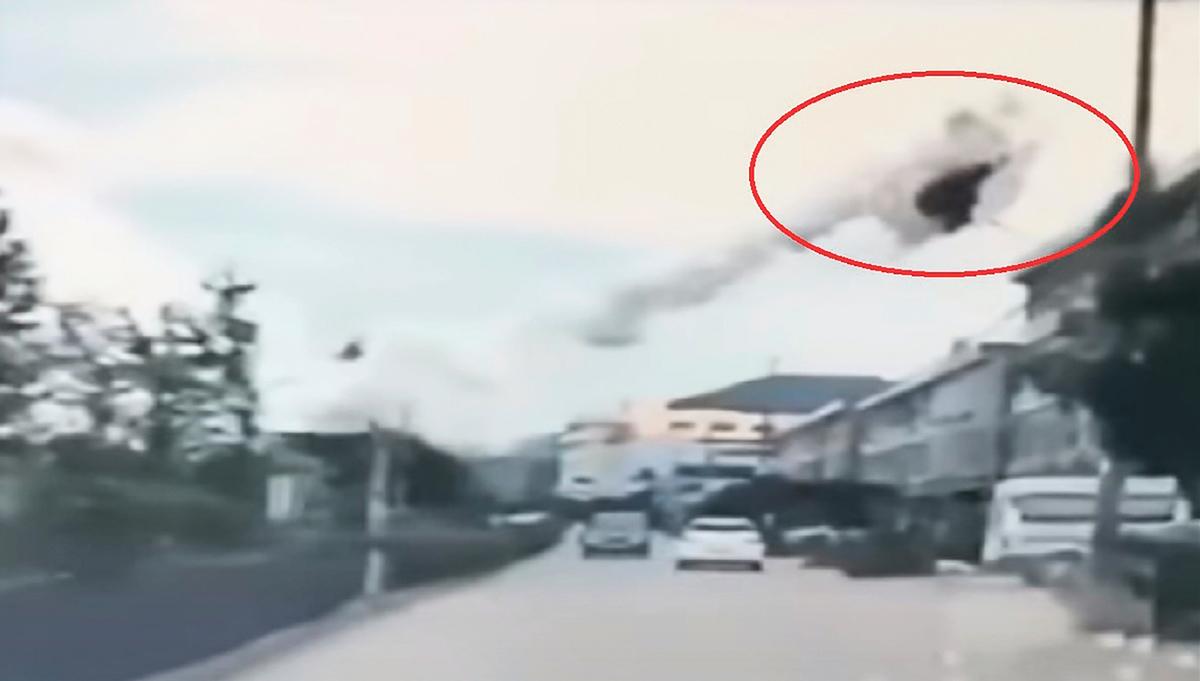 溫嶺油罐車爆炸即時影片顯示, 被炸飛的部份車體,隨著震波越過數條行車線,飛至路旁四層高民房屋頂。(影片截圖)