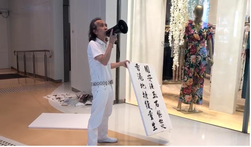 市民梁先生,舉起寫著「國安法玉石俱焚  香港地劫後重生」的告示牌,參加旺角新城市廣場的「父親節和你shop」活動。(梁珍 / 大紀元)