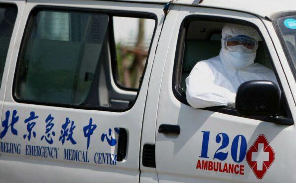 一名身穿隔離服的醫院工作人員坐在北京地壇醫院的救護車上。示意圖。(Feng Li/Getty Images)