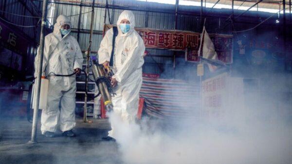 圖為2020年5月6日,綏芬河工作人員在消毒。(STR/AFP via Getty Images)