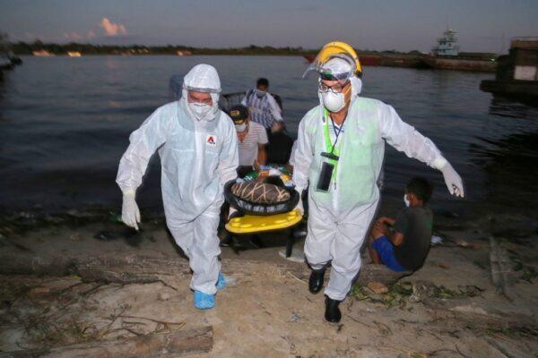2020年6月18日,醫務人員在秘魯洛雷托地區伊基托斯的亞馬遜河港口從船上帶下來一名11歲的中共肺炎患者,並將其轉移到該地區的醫院。(CESAR VON BANCELS/AFP via Getty Images)
