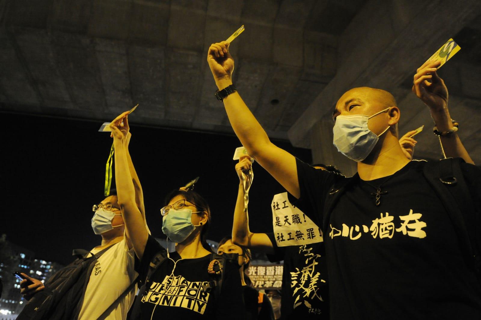 社工們拿出社工證,表示希望社工界明天在高等法院繼續撐劉家棟。(宋碧龍/大紀元)