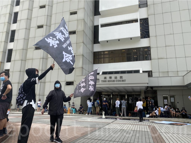 庭外有市民揮舞「光復香港 時代革命」的旗(霄龍/大紀元)