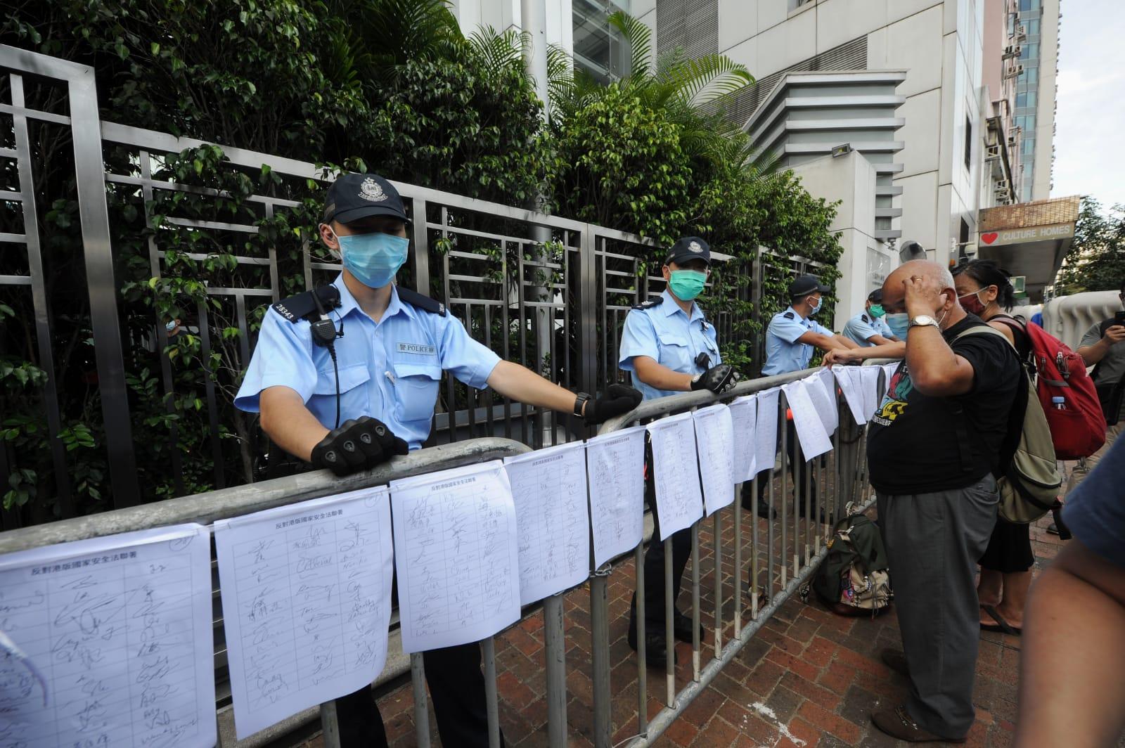 社民連將早前收集的2萬多個反「國安法」的聯署貼在中聯辦大樓外的鐵柵欄(鐵馬)上,有數十名全副武裝的警員在中聯辦外戒備。(宋碧龍/大紀元)