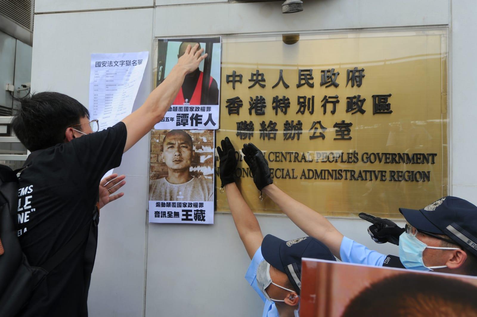 社民連將被中共關押人士圖片貼在中聯辦大樓外的鐵柵欄(鐵馬)上,有數十名全副武裝的警員在中聯辦外戒備。(宋碧龍/大紀元)