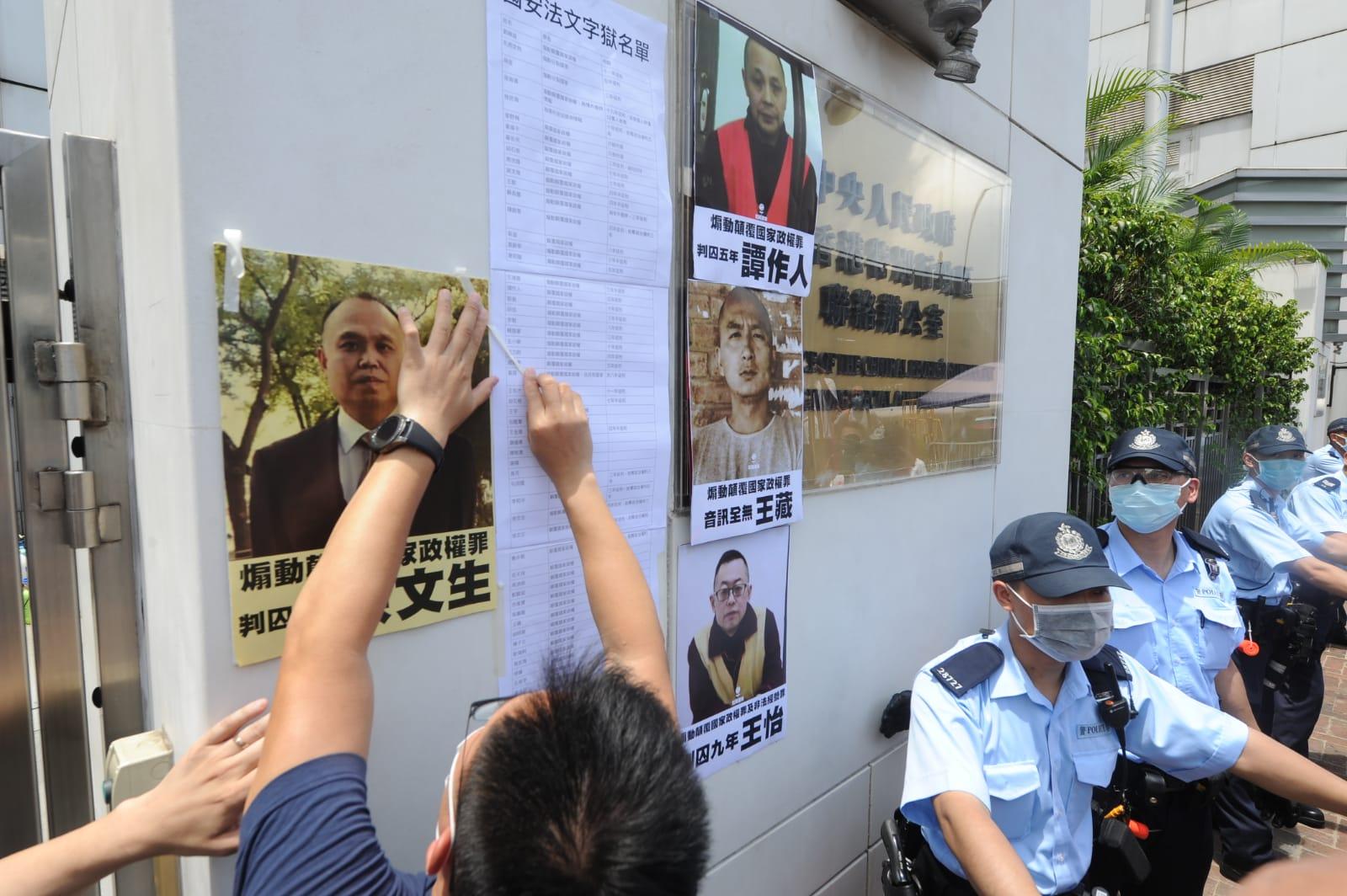 社民連將「文字獄名單」貼在中聯辦大樓外牆上,有數十民警力在旁戒備。(宋碧龍/大紀元)