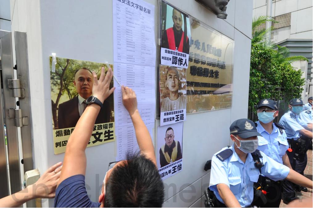 6月25日端午節,十餘名社民連成員前往中聯辦抗議「港版國安法」,將因「國家安全」罪名被判入獄的大陸政治犯名單貼在中聯辦外牆。(宋碧龍/大紀元)