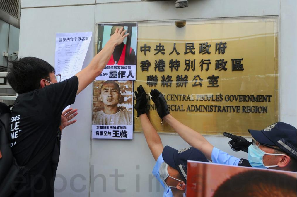 6月25日端午節,十餘名社民連成員前往中聯辦抗議「港版國安法」,將因「國安」罪名被捕入獄的大陸政治犯名單及照片貼在中聯辦外牆,警察試圖阻攔。(宋碧龍/大紀元)