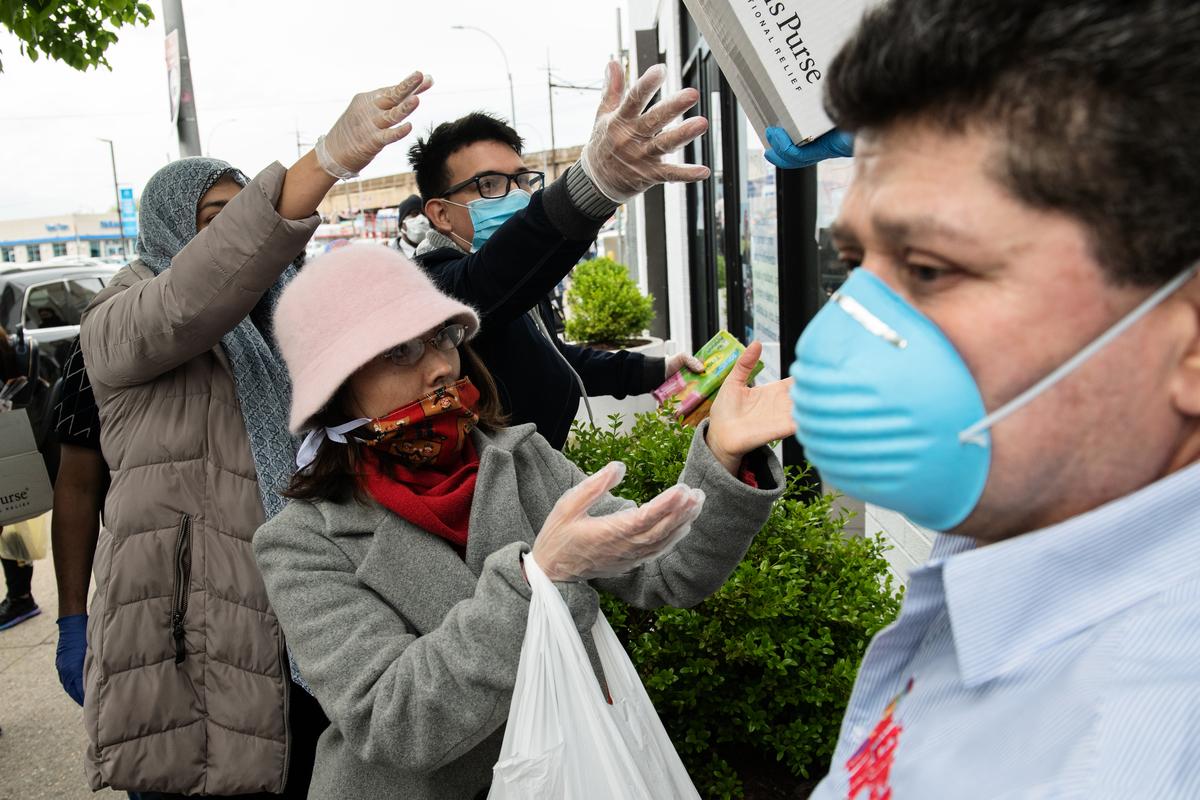 受中共病毒疫情影響,2020年世界經濟將萎縮約5%。圖爲今年5月06日,人們在紐約皇后區領取捐贈的雜物品。(Bryan Thomas/Getty Images)
