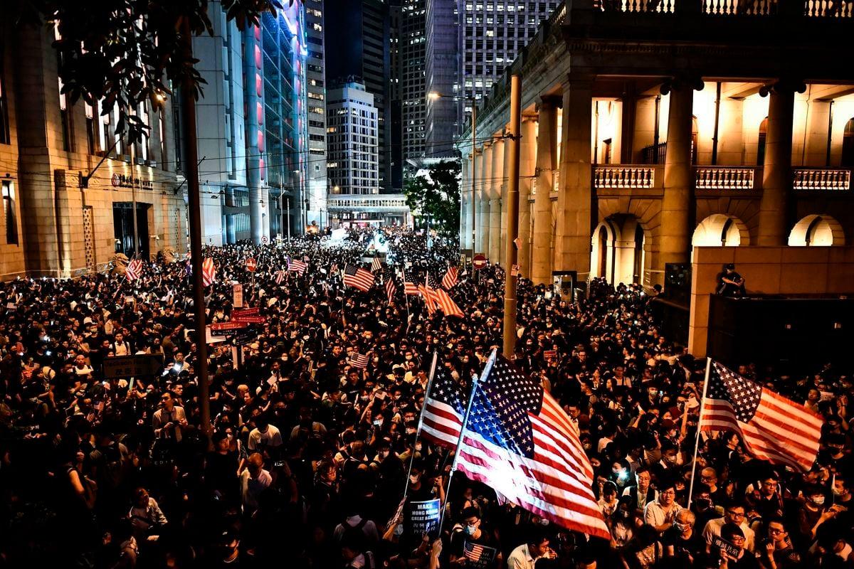 爲反對中共強推「港版國安法」制裁中共官員,美參議院全票通過《香港自治法》。圖爲2019年10月14日,揮舞美國國旗的香港抗議民衆。(圖:ANTHONY WALLACE/AFP via Getty Images)