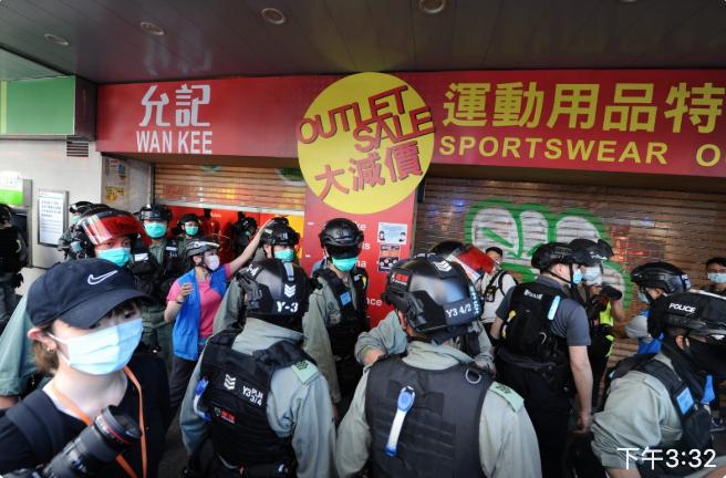 一運動用品店被大量防暴警察搜查,防暴警察開咪要求市民離開。(宋碧龍/大紀元)