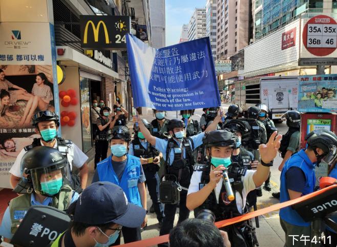 防暴舉咪警告,舉藍旗和驅趕民眾。(宋碧龍/大紀元)